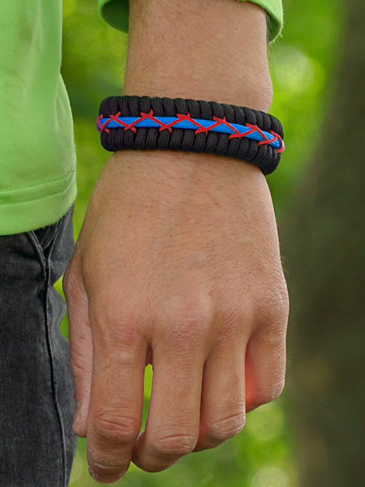 Lifestyle photo Black, Red & Blue Paracord Bracelet Track With Fire Starter, Compass and Whistle