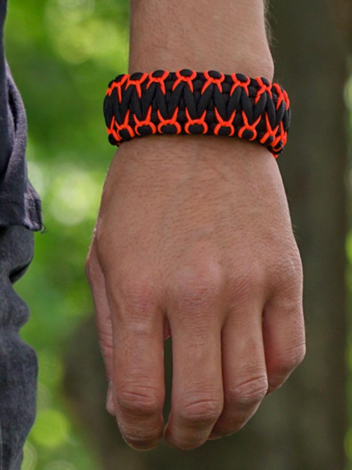 Suchen Sie ein originelles und außergewöhliches Geschenk? überrascht den Beschenkten sicher Schwarzes und oranges Paracord-Armband Krieger mit Messer, Anzünder, Kompass und Pfeife
